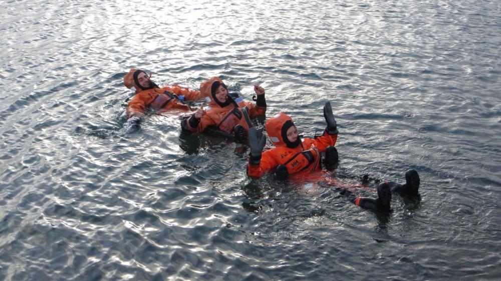 Auf der Suche nach dem Schatz im Hafenbecken in Überlebensanzügen