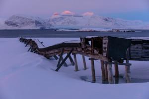 Ein fahler Streif liegt um Mitternacht über den Bergen im Kongsfjord
