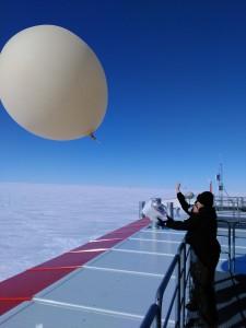 AWI-Überwinterer Andrea Rau und Marcus Heger (36. Überwintererteam) lassen eine Ozonsonde vom Dach der Neumayer-Station III steigen. Foto: Gerd König-Langlo