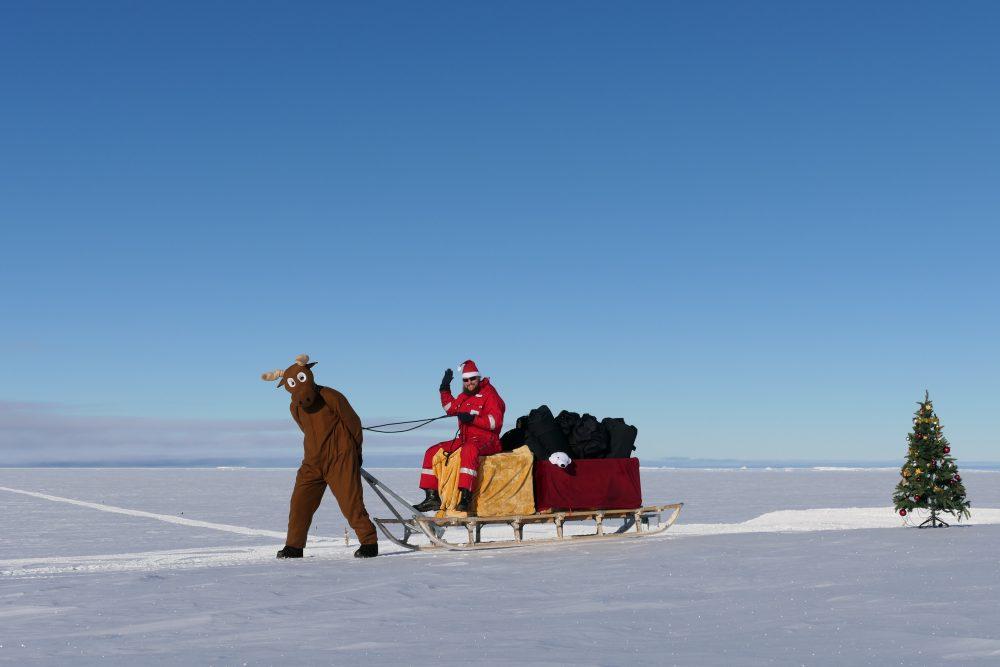 Weihnachtsmann auf Schlitten im Schnee.