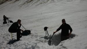 Im Vordergrund - Ausheben eines Schneeschachts. Im Hintergrund - Arbeit mit einem Snow Liner.