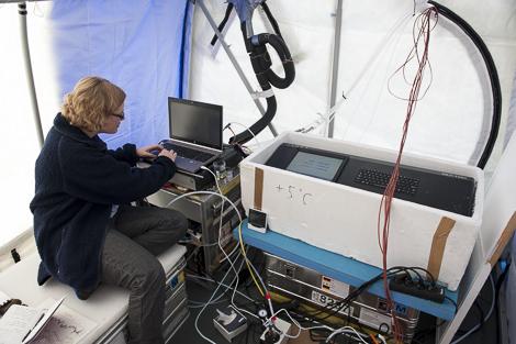 Melanie neben ihren Messgeräten im kleinen Zelt