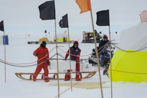 Jan und Philipp beim Tragen von Eiskernkisten. Sepp auf dem Skidoo. Sverrir im Zelt, Holger mit Pistenbully