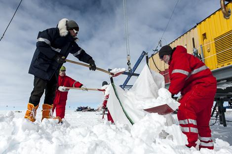 Martin, Thomas, Melanie und Michael schaufeln Schnee in den Transportsack der Schneeschmelze