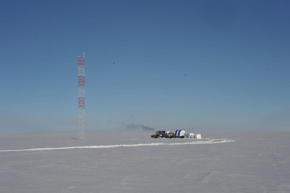 Cofi-Traversen-Zug vor dem markantesten Wahrzeichen der Plateau Station: ein meteorologischer Mast, der in der Sommersaison 1965/66 errichtet wurde, ursprünglich 32 m hoch war und jetzt immer noch fast 29 m hoch ist.