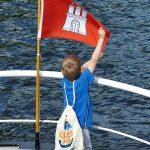 Junge hält Flagge fest