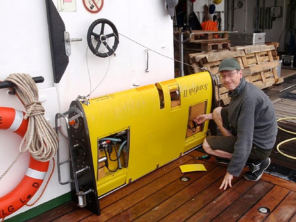 Mann arbeitet an einem Messgerät an Bord eines Schiffes