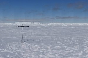 Photo 2: The first successful deployment of the snow height buoy (left) and the ice mass balance buoy (right) and an ice berg in the background. Photo: Leonard Rossmann.