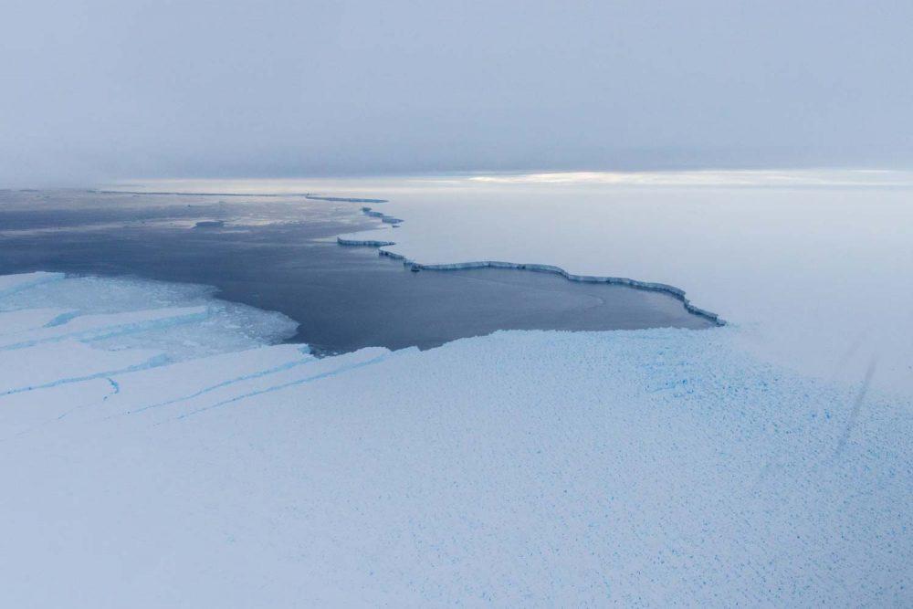 Polarstern nahe der Schelfeiskante. Der unebene, bläuliche Teil des Gletschers ist ein Gebiet schnell fließenden Eises. Foto: Alfred-Wegener-Institut / Thomas Ronge