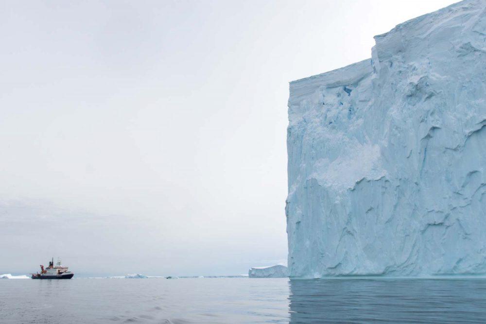 Ein massiver Eisberg lässt Polarstern winzig erscheinen. Foto: Alfred-Wegener-Institut / Thomas Ronge