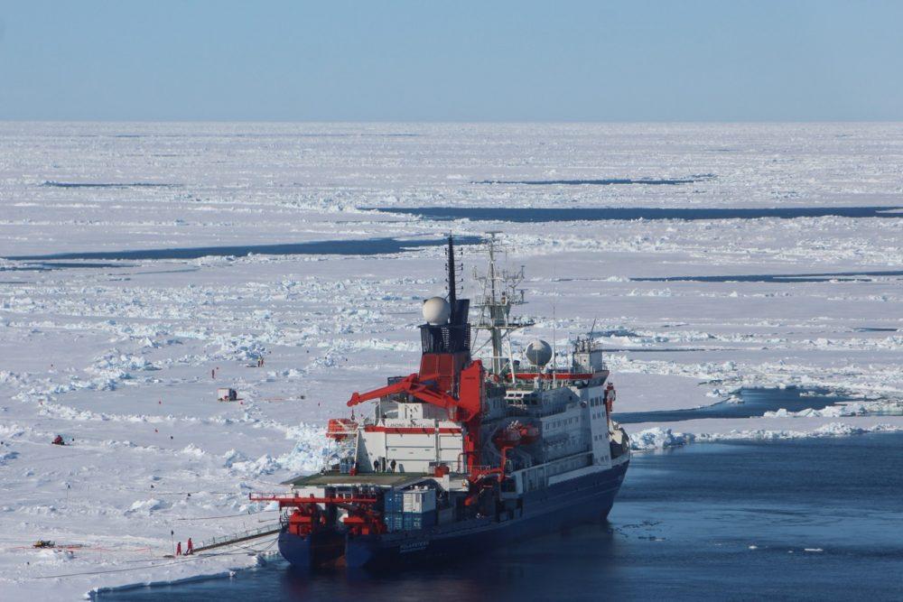 Polarstern liegt während der Driftstation (Expedition PS106) an einer Scholle. Auf der Backbordseite markieren verschiedene Installationen und Flaggen die unterschiedlichen Messpunkte auf und unter dem Meereis (Foto: Svenja Kohnemann).