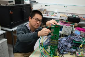 Wenxiong working on an electronic device