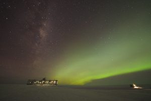 Polarlichter und Nachthimmel über der Neumayer-Station III in der Antarktis